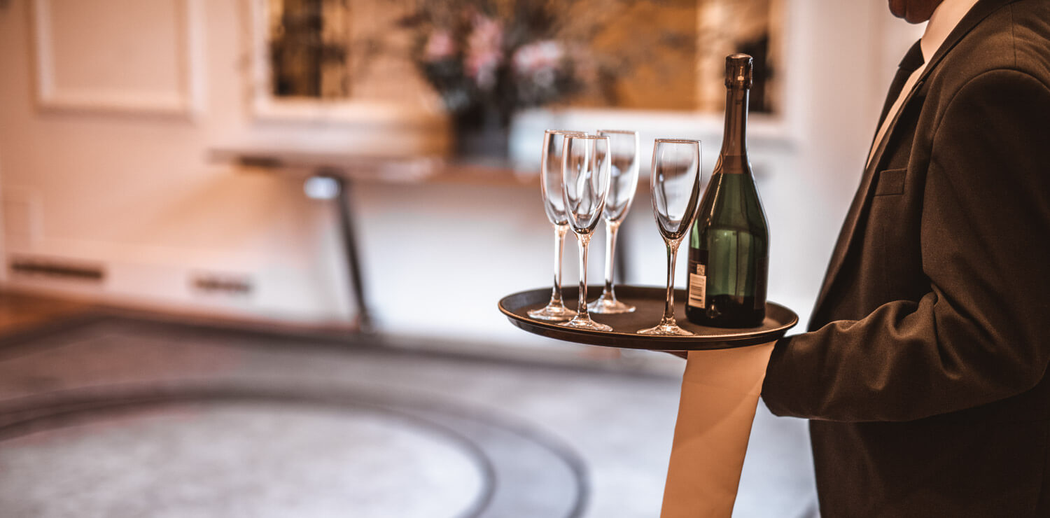butler-carrying-wine-bottle-and-glasses | The Savoy Hotel on Little Collins