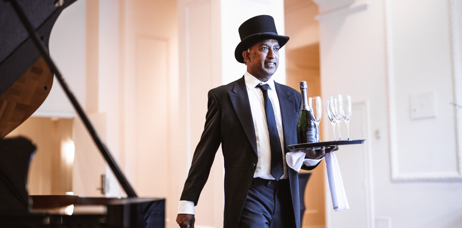 waiter-in-top-hat-carrying-champagne-and-glasses | The Savoy Hotel on Little Collins
